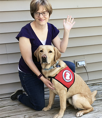 woman waving with yellow lab dog in service cape