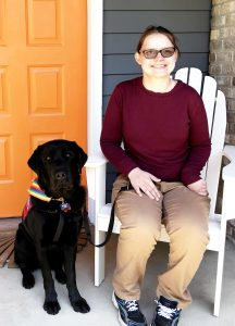 black lab dog and young woman sitting on porch