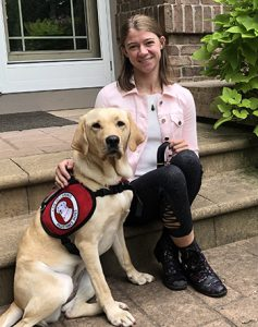 yellow lab service dog with young woman on front steps