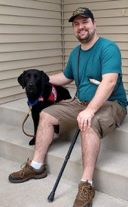 black lab service dog and man sitting on front steps
