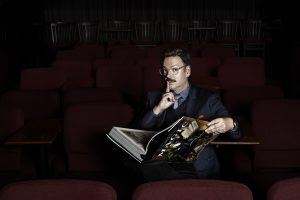 man sitting in theater holding magic book and whispering