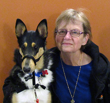 collie dog with woman in black jacket