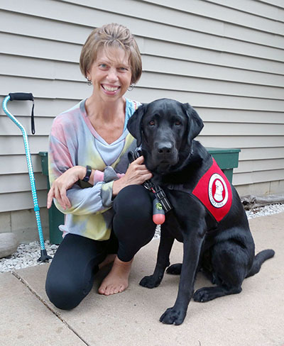 woman with black lab service dog