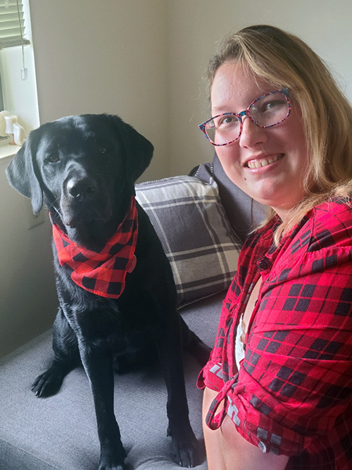 black dog wearing bandana and woman in red and black shirt