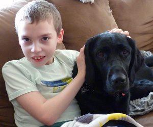 boy sitting on sofa with black dog