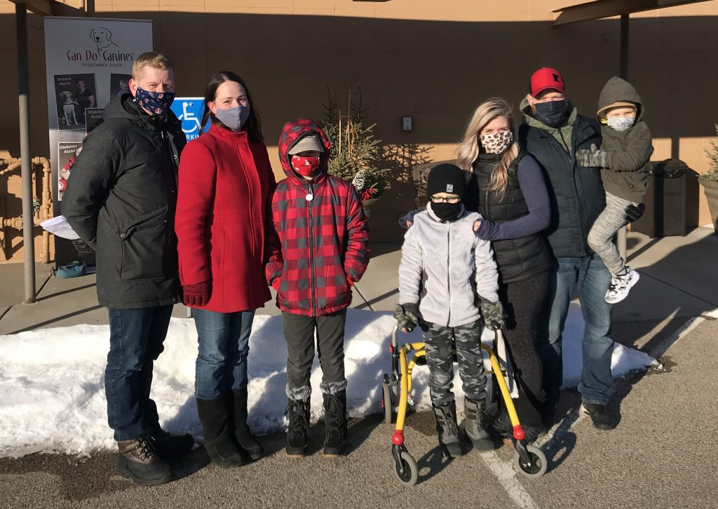 six people with facemasks in parking lot