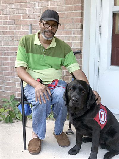 man sitting outside with black service dog