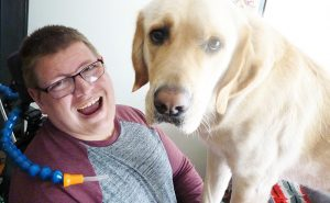 young man laughing with large white dog
