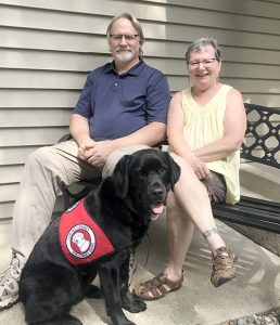 man and woman sitting outside home with black service dog