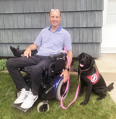 man using a wheelchair next to a service dog
