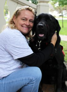 woman sitting on porch steps with black dog