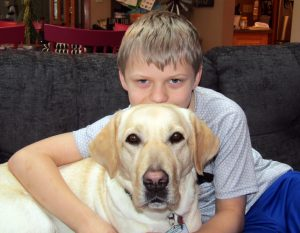 boy hugging yellow lab dog from behind