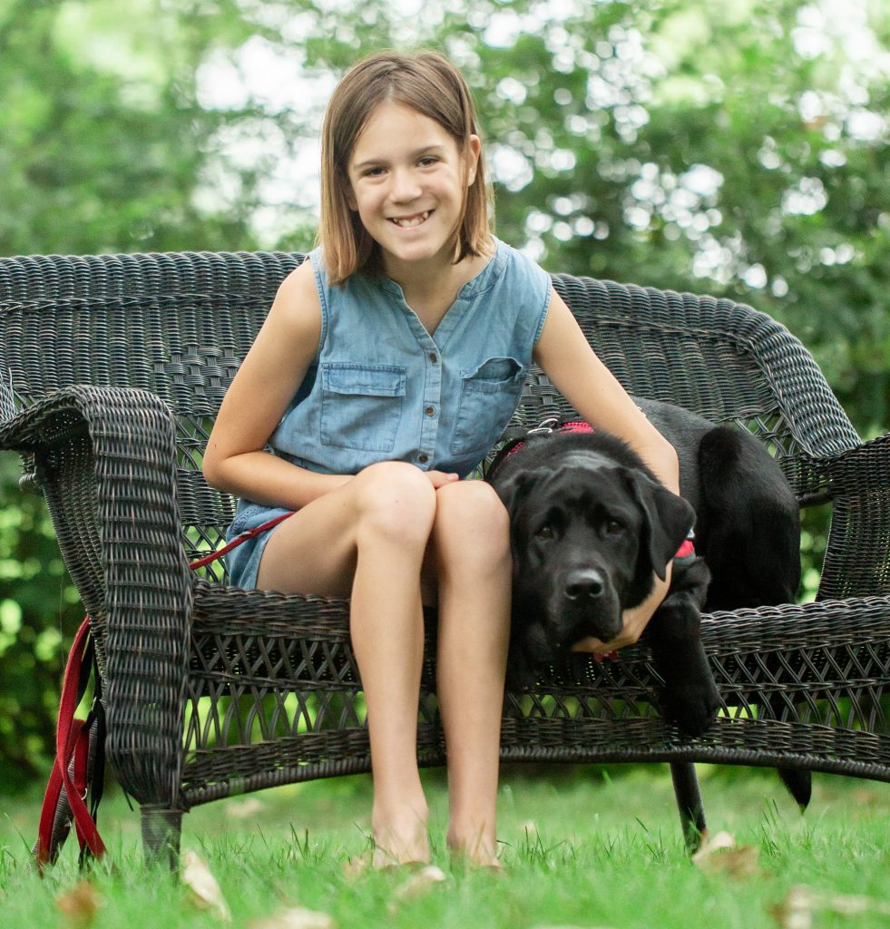 girls and black dog sitting on outside bench