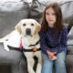 young girl and service dog sitting on couch