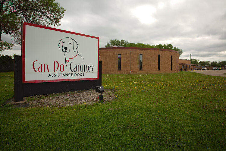 Can Do Canines sign with building in background