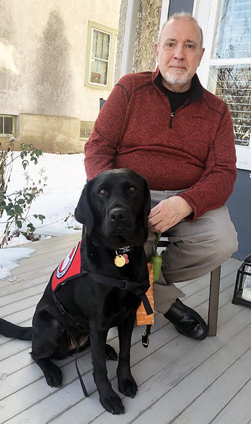 man sitting with black lab dog