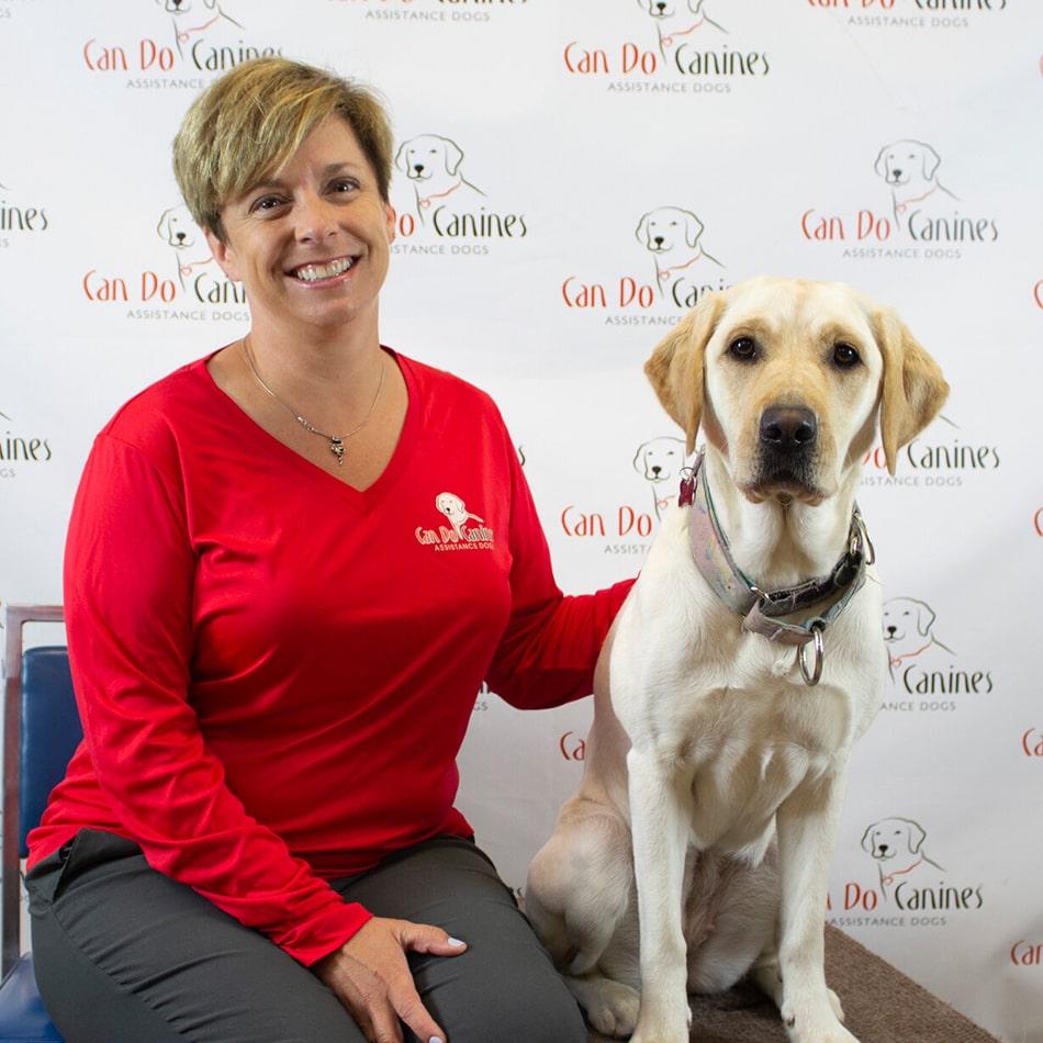 Denise Yokom sitting with a dog