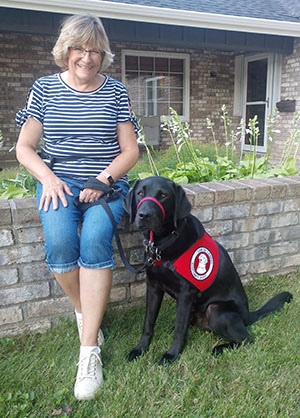 woman and black service dog sitting outside
