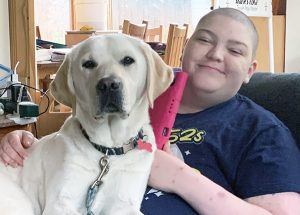 yellow lab and woman sitting together on chair
