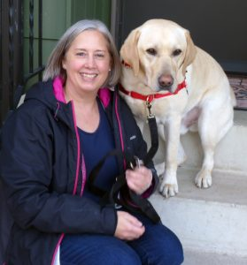 woman sitting on front steps with yellow lab