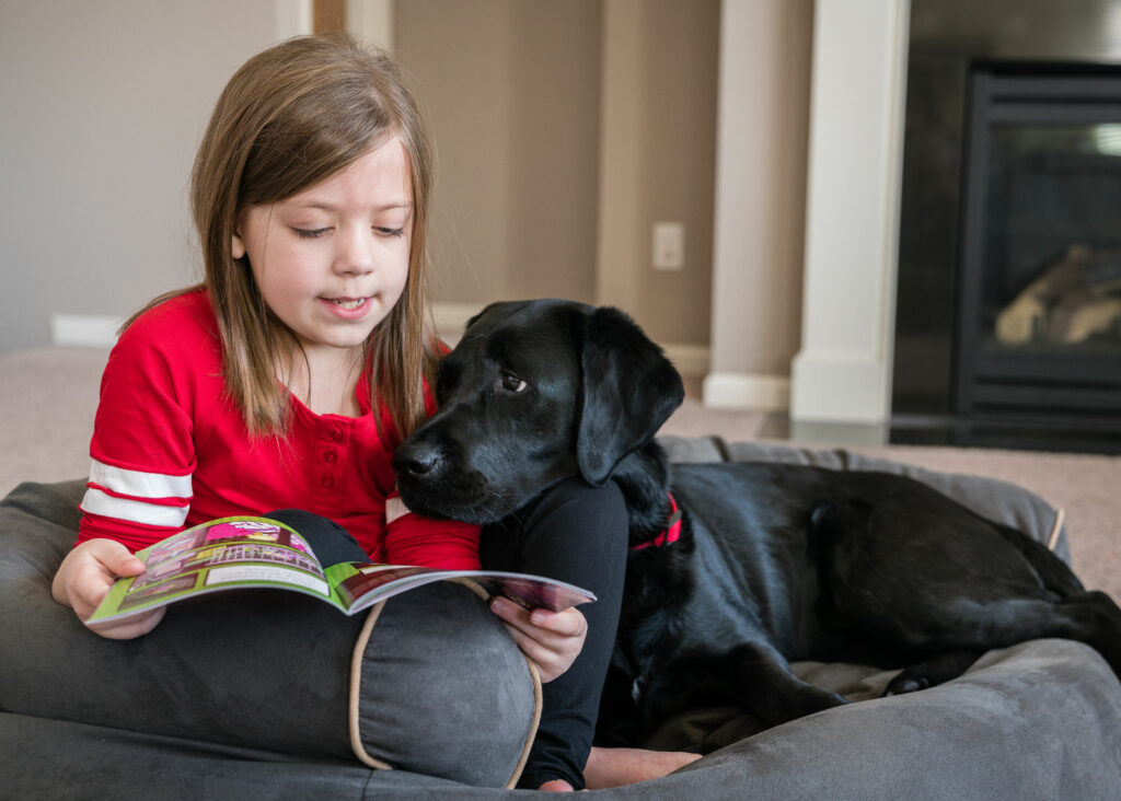 young girl reading book to black Lab dog