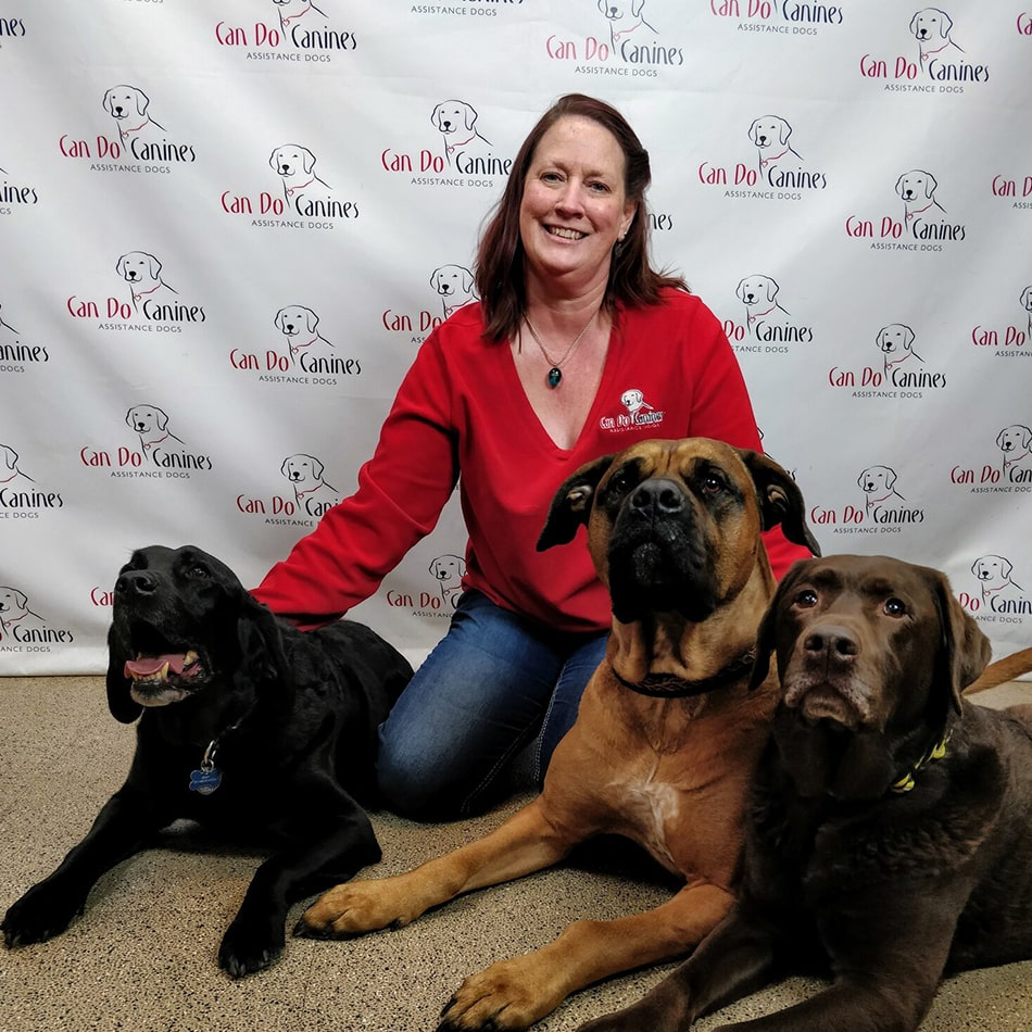Leslie Flowers sitting with three dogs on the floor