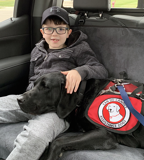 boy and black Lab service dog sitting in back seat of car
