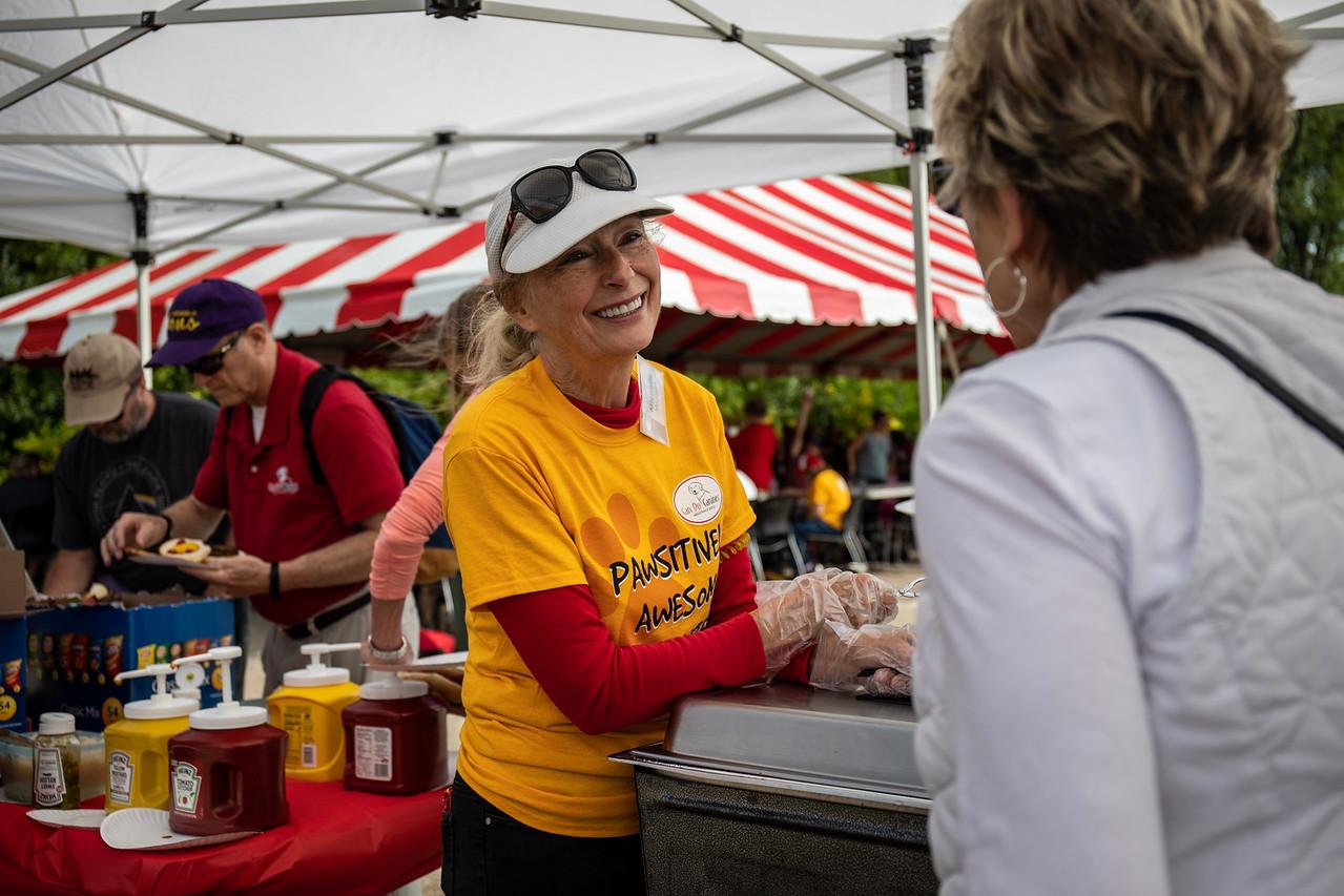 volunteer interacting with person in outdoor tent