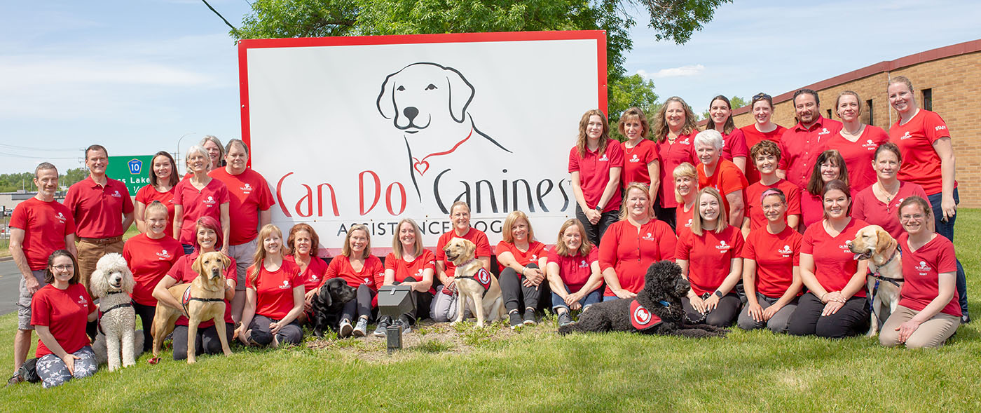 Dozens of people in red shirts outside in front of Can Do Canines sign