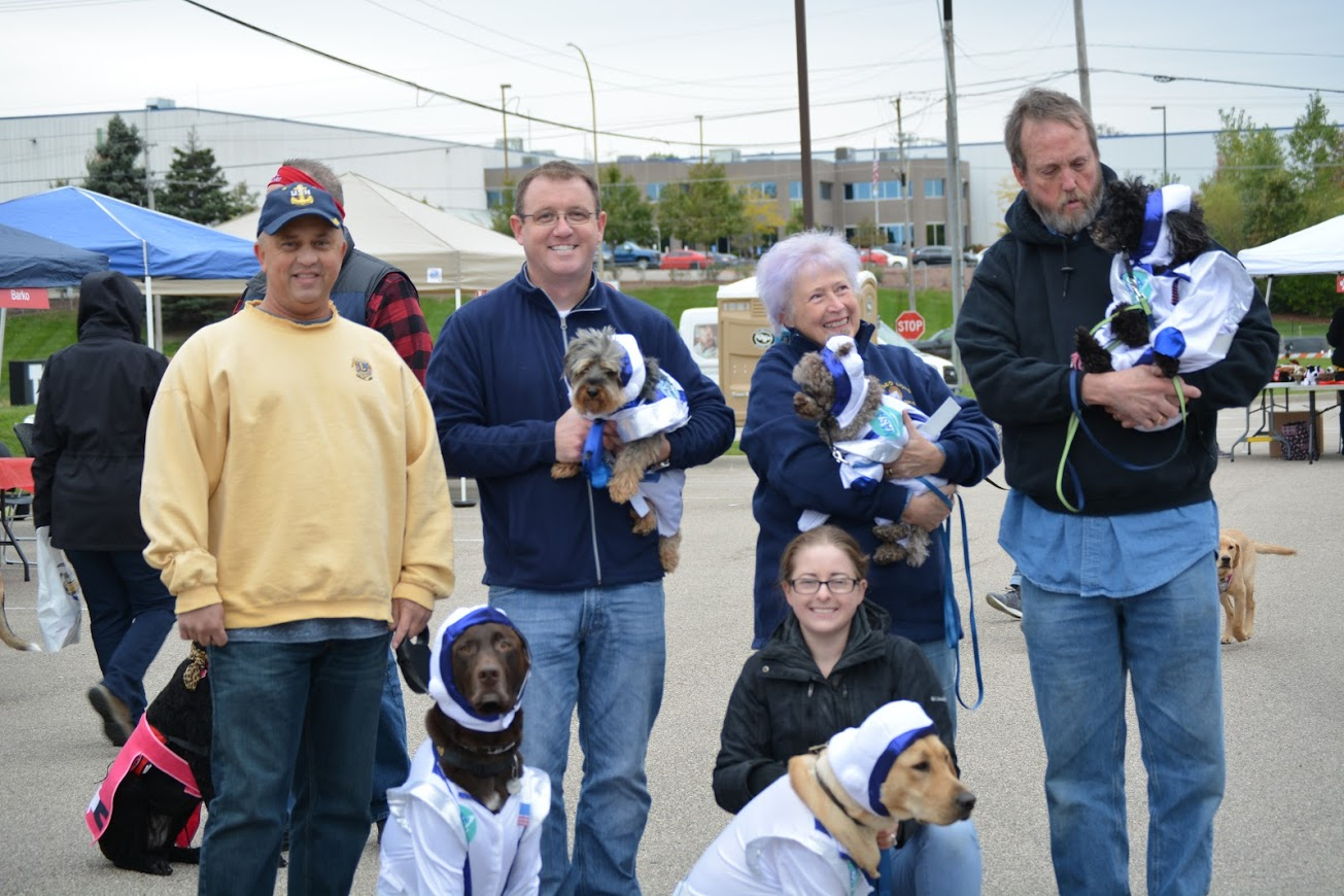 five adults with several dogs in parking lot
