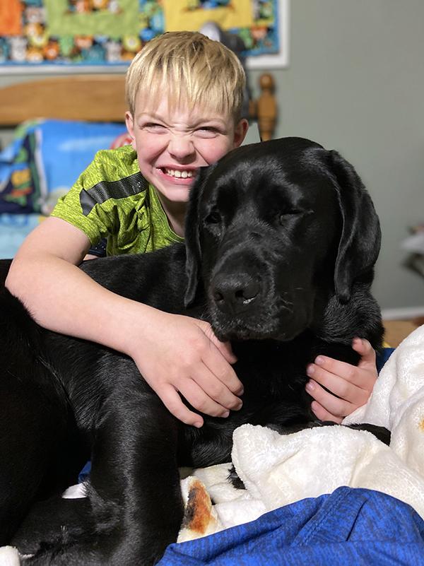 boy with big smile hugging large black dog on bed