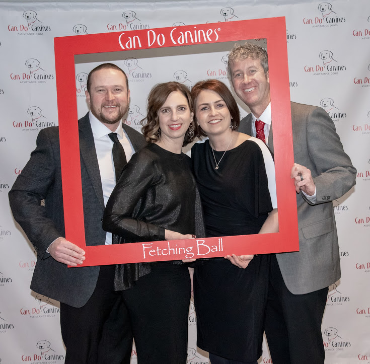 Two men and two woman standing inside a giant photo frame for Can Do Canines