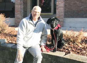 man and large black dog sitting on retaining wall outside