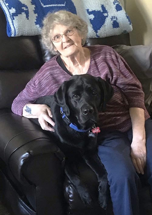 woman and large black dog sitting in recliner together