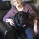 woman sitting with large black dog in recliner
