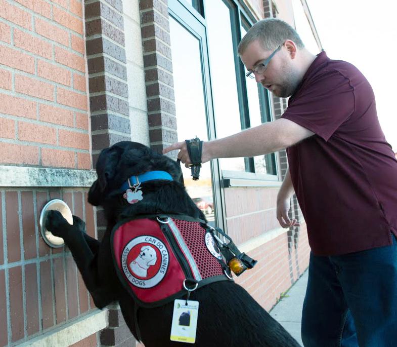 man instructing service dog to press door pushplate