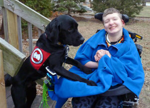 boy in wheelchair with large black service dog putting front paws on him