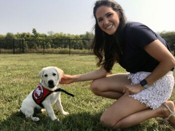 Woman sitting with yellow lab puppy in cape
