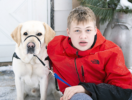 yellow Labrador and teenager boy sitting outside