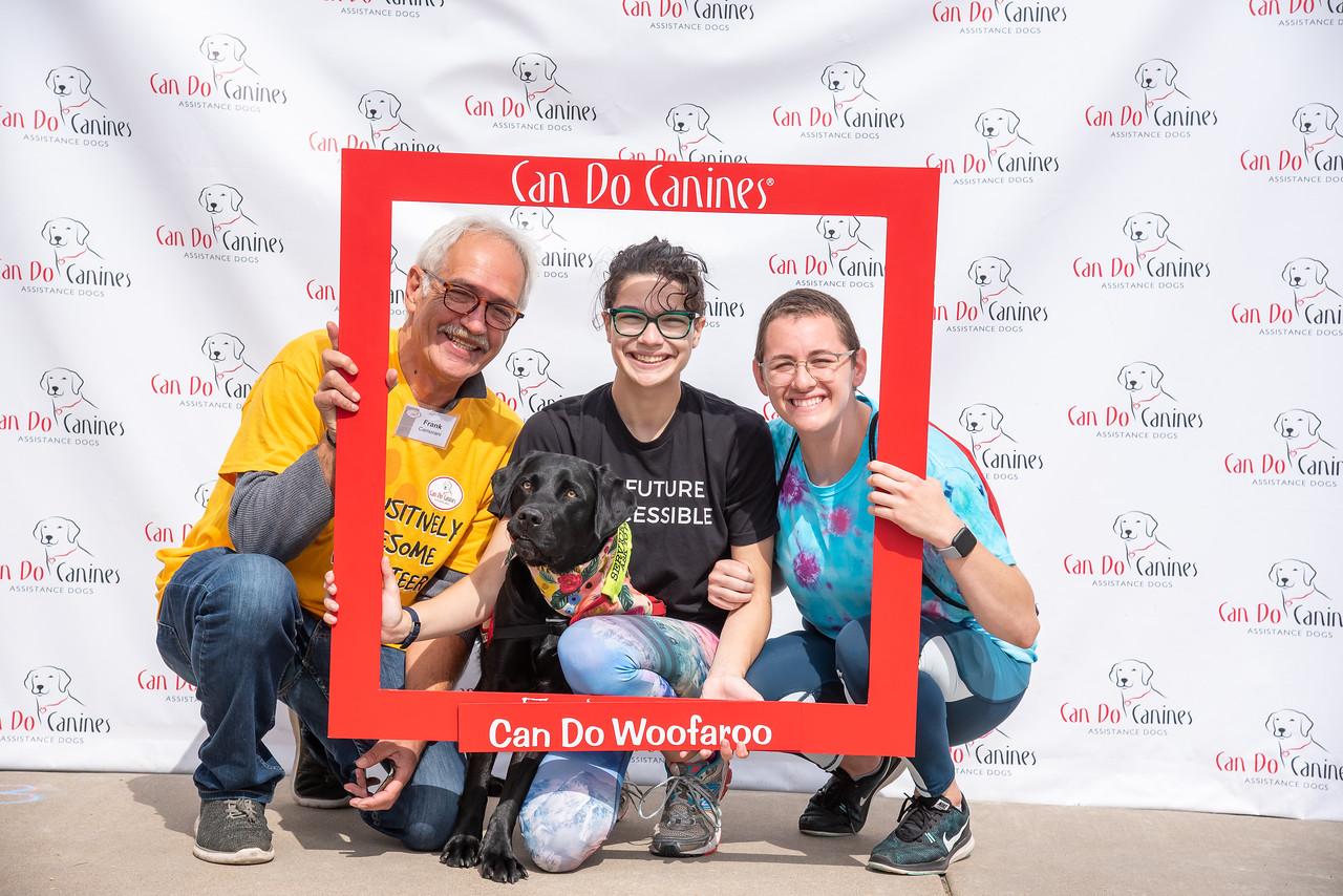 three people and black dog holding large photo frame around them