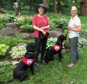two women and two service dogs in back yard