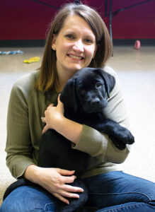 woman sitting on floor holding black puppy