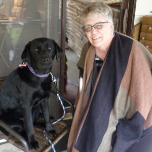 woman standing next to large black dog sitting on patio chair