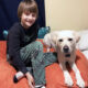 boy and large white dog sitting together on bed