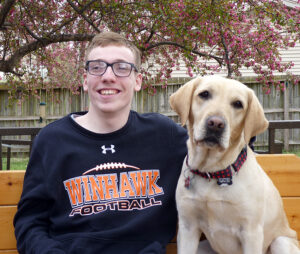 young man and yellow Labrador Retriever sitting on bench outside