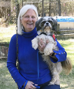 woman in sweater holding small dog outside