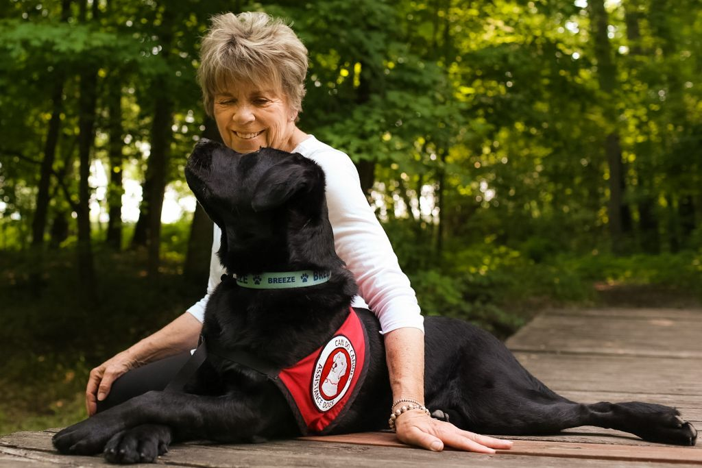 woman sitting outside and looking into eyes of large black service dog