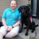 man in turquoise shirt sitting on front steps with black service dog