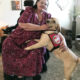woman in wheelchair with large service dog putting front paws on her leg