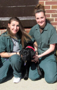 two female prison inmates kneeling outside with black puppy between them